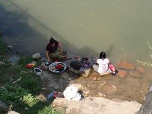 Kvinner vasker klær ved elva